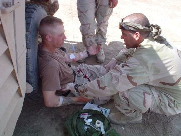 Patrick R McCaffrey giving IV to another soldier.
